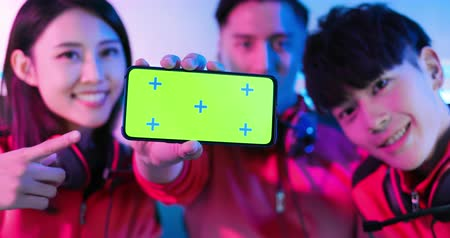 Team of asian teenage cyber sport gamers show app game on the 5g smartphone with green screen