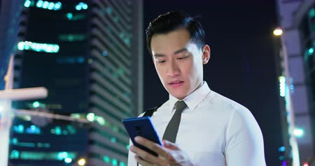 biznesmen : businessman use the smart phone and feel excited with fist gesture