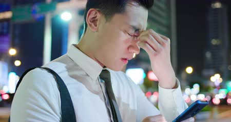 lesion : asian businessman feel eye tired while using smartphone on the street in the evening Stock Footage