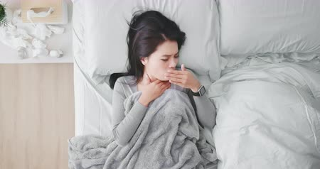 cold and flu : High angle view shot of asian woman sick and cough in the bedroom