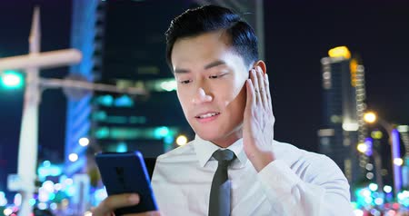 wearing earphones : asian man wear wireless earbuds on and to listen music on the street Stock Footage