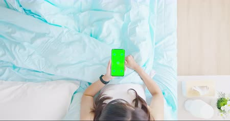 flat lay : overlooking of asian woman use smartphone with green screen on the bed in the room