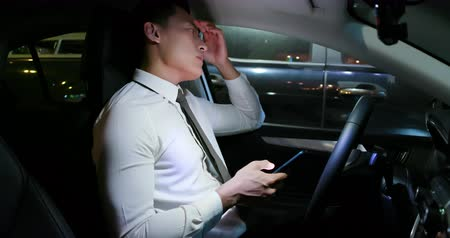 abused : asian businessman feel tired and depressed after using smartphone in the car Stock Footage