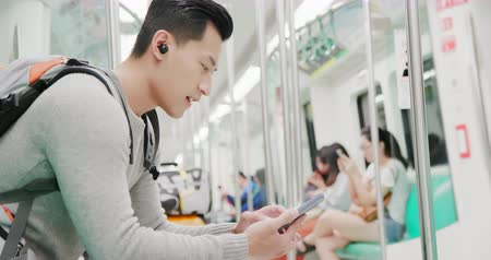 verdadeiro : asian man speak to phone with wireless earbuds on the mrt