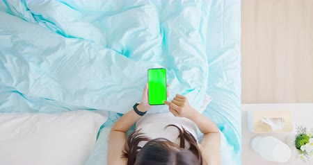 mobile game : top view of asian woman use smartphone with green screen on the bed in the room