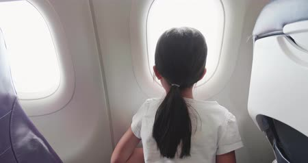 see off : little girl watch outside through the window on the airplane