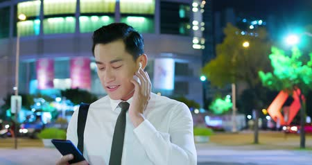 telefonda : asian man speak to phone by wearing wireless earbuds while walking on the street Stok Video