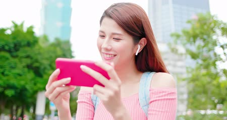 wearing earphones : asian woman watch video with 5g smartphone outdoor-location taipei and taiwan