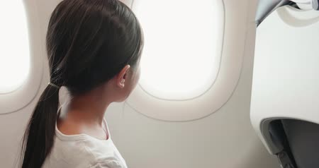 pónei : little girl take airplane and look outside the window