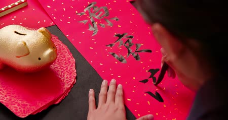 skarbonka : asian people write calligraphy on couplet to celebrate chinese new year with word meaning rich Wideo