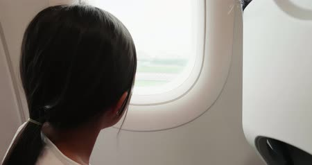 see off : little girl take airplane and look outside the window