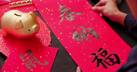 skarbonka : asian people write calligraphy on couplet to celebrate chinese new year with word meaning luck