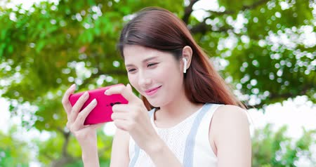 wearing earphones : young asian woman watch video and wear wireless earbuds with her smart phone in the park Stock Footage