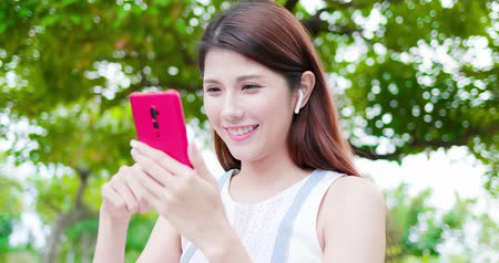 wearing earphones : young asian woman use the phone and wear wireless earbuds in the park Stock Footage