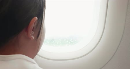 see off : close up of little girl take airplane and look outside the window