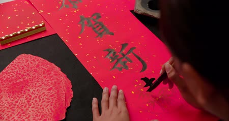 significado : asian people write calligraphy on couplet with word meaning happy chinese new year Stock Footage