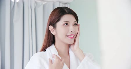 hand on chin : beauty asian girl touch her good skin on face and look mirror in the bathroom Stock Footage