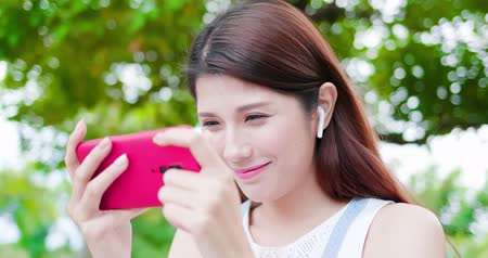 ouvir : young asian woman watch video and wear wireless earbuds with her smart phone in the park Stock Footage