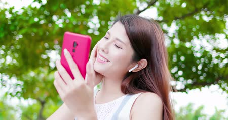 wearing earphones : young asian woman listen to music with wireless earbuds and her smart phone in the park Stock Footage