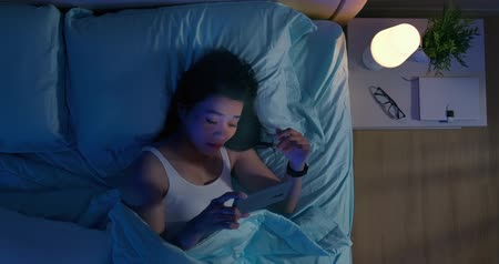 optometria : High angle view shot of asian woman has eye pain and feel tired because watching smartphone in dark at night