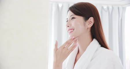 crema corporal : beauty asian woman apply moisturizer lotion on her face in the bathroom Archivo de Video