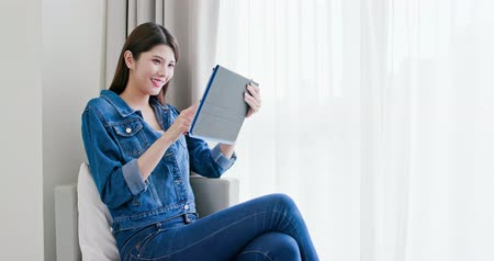 néz : asian woman sit on sofa and use tablet at home