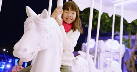 recreational park : asian girl is having fun on a carnival carousel Stock Footage