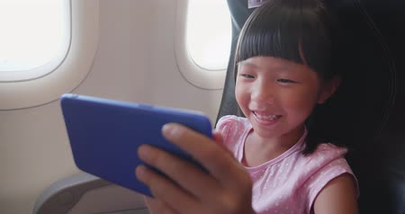 aircraft cabin : Girl play mobile game happily on the airplane Stock Footage