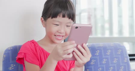 сотовый телефон : little girl play mobile game happily on the bus-location okinawa and japan