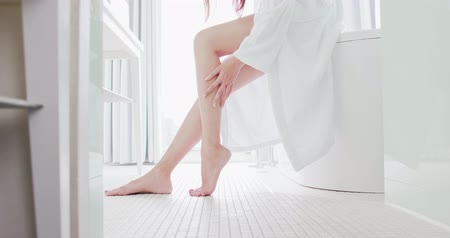 buzağı : Asian young woman massage leg gently in bathroom