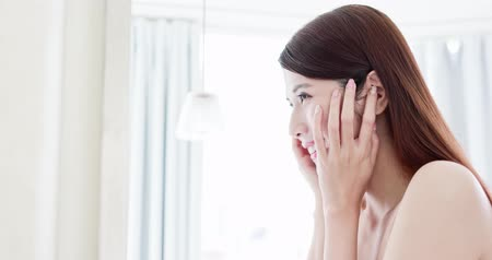 hand on chin : beauty asian girl touch her good skin on face and look mirror at home Stock Footage
