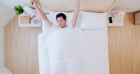 lays : Top view of young asian man sleeping well and relaxing in the morning
