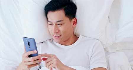 kilátás : overlooking of asian man use smartphone on bed in the morning