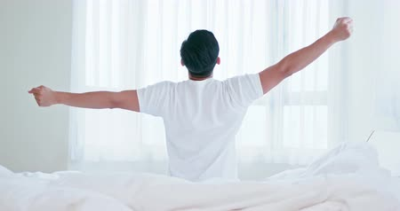 felébred : back view of asian man stretching arms on bed after wake up in the morning at home