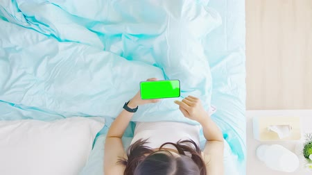 flat lay : Overhead view of asian woman watch video by smartphone with green screen on the bed in the room