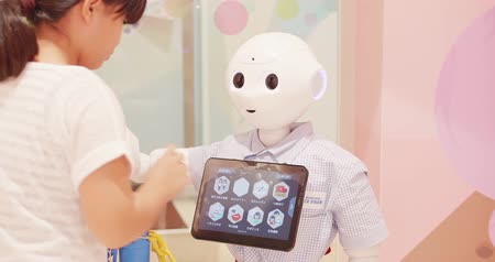 Okinawa, Japan-Aug 21, 2019: robot humanoid assistant with information screen in shop