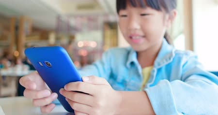 close up of asian little girl use smartphone happily in the restaurant Stock Footage