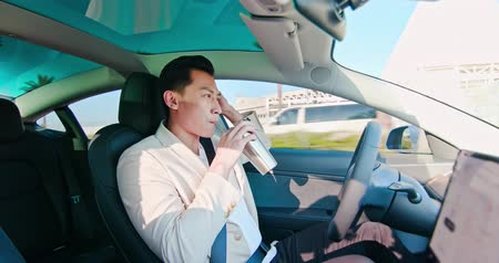 função : asian relaxed man use reusable eco-friendly ecological straw to drink while riding an autonomous self driving electric car and turn on autopilot function