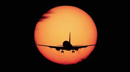 front cover : Jet plane landing with sun behind it Stock Footage
