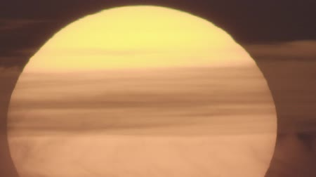 another : Ultra long shot of orange sun with clouds, no color