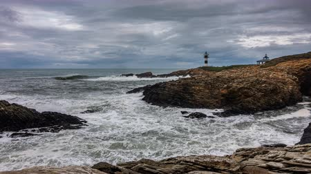 Rough coastline ocean with lighthouse time lapse Stock Footage