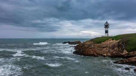 Rough coastline with lighthouse time lapse under the cloudscape Stock Footage