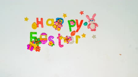 festa : Children make holiday inscription from plasticine and confetti Happy Easter, a motion stop