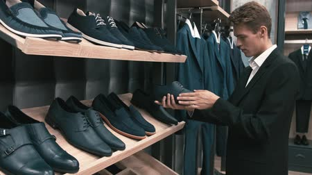 ubrania : Man buys classic clothes and shoes in shop