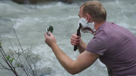 dýka : a man shaves a knife at a mountain river