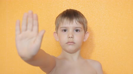 the boy makes a gesture with his hand Stop