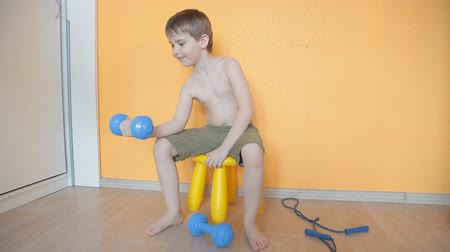 ügyesség : little boy doing dumbbell exercises on biceps, triceps