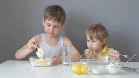песочное печенье : children roll out the dough and make cookies