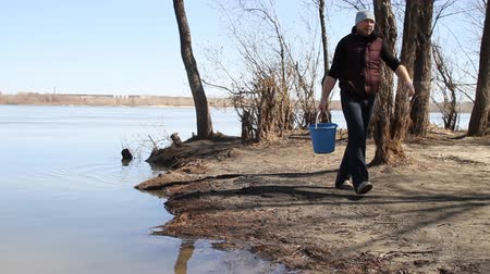 mopping : a man carries a bucket of water from the river and pours on the car Stock Footage
