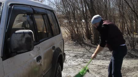 mopping : a man washing an SUV with a MOP and a rag from the bucket on the river